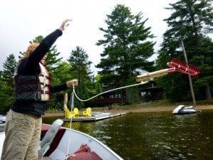 Hamilton County Soil and Water Conservation District's Caitlin Stewart checks Limekiln Lake for invasive plants by tossing a rake attached to a length of rope into the water, hoisting it back into the boat, and inspecting the tines for suspicious plants.
