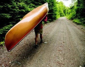A paddler portages a canoe along gulf brook road