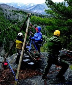 A ranger and two volunteers practice rescue techniques at a cliff near King Philip's Spring