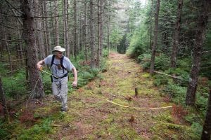 Peter Bauer measures a snowmobile trail near Newcomb.
