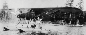 Merille Phoenix and his early floatplane on Witchhopple Lake in 1932 with Hartnett on the pontoon
