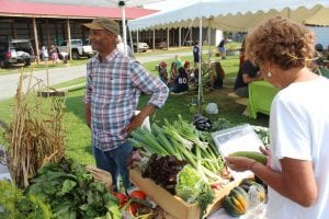 A customer makes her selections at a local vegetable grower's farm stand at the Adirondack Harvest Festival in Westport