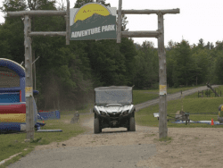 A utility vehicle traverses a Whiteface road in August