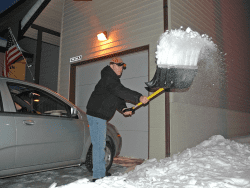 Phillip Bridges shovels the driveway of his new home