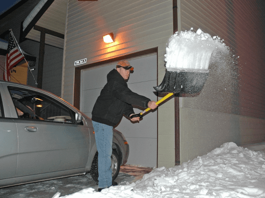 Phillip Bridges shovels the driveway of his new home