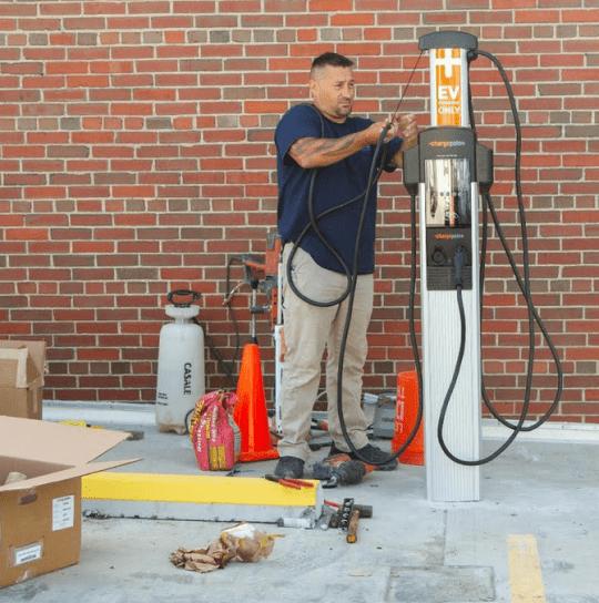 Rick Gorleski of PlugIn Stations Online installs an electric vehicle charging station at the Hotel Saranac