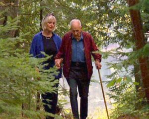 Barbara Glaser and Clarence Petty walk together in the woods near Camp Uncas, Raquette Lake.