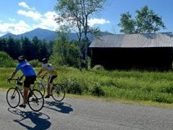 two bikers riding past a house and a mountain