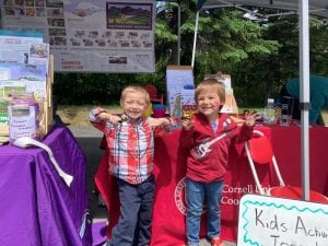 2 kids smiling in front of the power of produce stand at farmers market