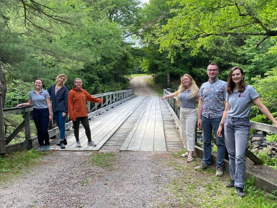Seasonal staff, (from left) Maddie, Katie, Amalia, Sophie, Randy, and Anna, are ready to welcome YOU to camp!
